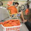 Royalty-Free Stock Photo: Portrait of man with team spirit at laundromat