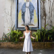 Hispanic woman in front of Virgin Mary mosaic - Stock Photo