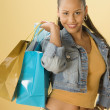 Studio shot of a female Dominican teenager holding shopping bags — Stockfoto