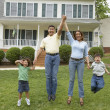 Family jumping together in front yard — Stock Photo