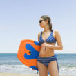 Stock Photo: Womholding boogie board at beach