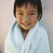 Young girl smiling wrapped up in towel — Stock Photo