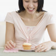 Asian woman and candle on cupcake — Stock Photo