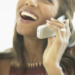 Close up of woman laughing while talking on cell phone — Stock Photo