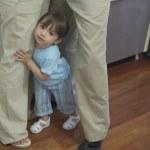 Toddler girl standing between legs of parents — Stock Photo #13239227