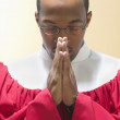 Man in choir robe praying — Stock Photo