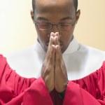 Man in choir robe praying — Stock Photo
