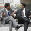 Royalty-Free Stock Photo: Two businessmen talking on outdoor bench