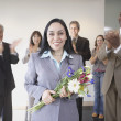 Businesswoman holding flowers while co-workers applaud — Stock Photo