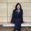 Asian businesswoman sitting on bench indoors - Stock Photo