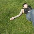 Asian woman listening to mp3 player in grass — Stock Photo #13239310