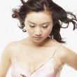 Studio shot of Asian woman with hair blowing - Stock Photo