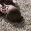 Young girl lying on floor talking on cell phone - Stock Photo