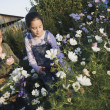 Stock Photo: Two Pacific Islander girls picking wildflowers with basket