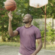 Man spinning basketball on finger - Stockfoto