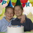 Portrait of two boys hugging with cake at birthday party — Stock Photo