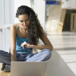Portrait of young woman with laptop in hallway - Stockfoto