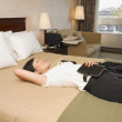 Asian businesswoman laying on hotel bed — Foto Stock