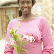 Smiling woman holding flowers — Stock Photo