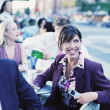Businesswoman at outdoor restaurant laughing — Stock Photo #13239450