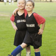 Portrait of two boys on soccer field with ball - Stock Photo