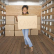 African girl holding box in moving truck — Stock Photo