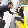 Businesswoman paying cab fare - Stock Photo