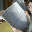 Stock Photo: Businesswoman reading newspaper