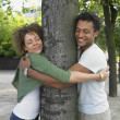 Couple smiling and hugging tree — Stock Photo