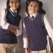Two school girls in uniform smiling — Stock Photo
