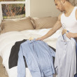 Hispanic man picking out a shirt in the bedroom — Stock Photo