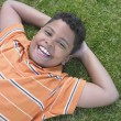 Indian boy laying in grass smiling — Stock Photo #13239612