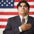 Stock Photo: Businessmstanding in front of Americflag with one hand across his heart