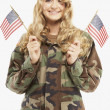 Woman wearing military uniform and holding American flags — Stock Photo