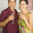 Portrait of Hispanic couple holding wine in kitchen — Stock Photo