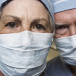 Stock Photo: Close up of senior male and female doctors in surgical masks