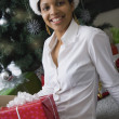 African woman wearing Santa Claus hat next to Christmas tree — Stock Photo