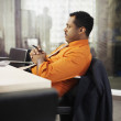 African businessman sitting at desk — Stock Photo