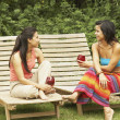 Two young women sitting outdoors — Stock Photo