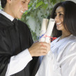 Graduating man and woman holding diplomas - Stock Photo
