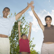 Stock Photo: Portrait of family with hands raised