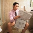 Businessman reading newspaper while sitting on toilet - Stock Photo