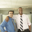 Businessmen smiling for the camera in empty office space — Stock Photo