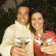 Hispanic couple toasting with cocktails at night — Stock Photo #13239817