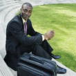 Businessman with briefcase sitting outdoors — Stock Photo
