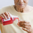 Close up of senior African woman pouring medication into cup — Stock Photo