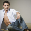 Stock Photo: Man sitting on floor with shirt unbuttoned