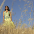 Woman walking among wild grasses - Stock Photo