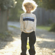 Young boy standing on gravel path — Foto Stock