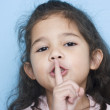 Portrait of girl with finger over mouth — Stock Photo #13239901